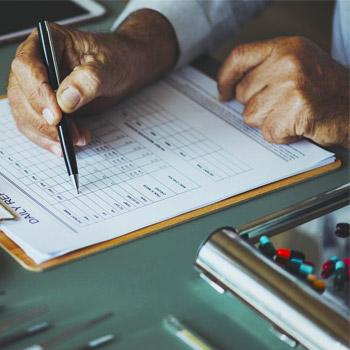 immagine di una mano che indica un documento con alcuni farmaci accanto
