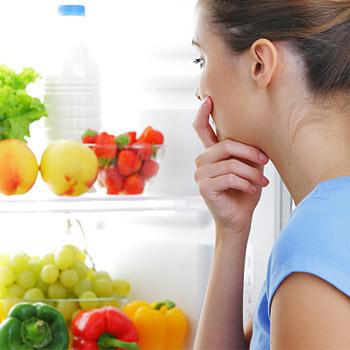 donna che osserva cibi nel frigo