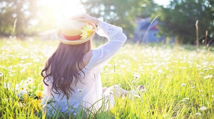 donna con cappello sul prato al sole