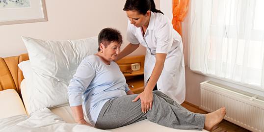 Immagine di un'infermiera che aiuta una paziente a sdraiarsi
